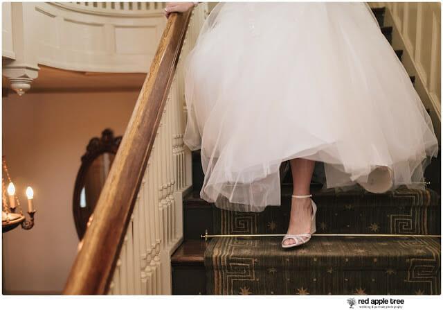 Bride walking down staircase in wedding dress