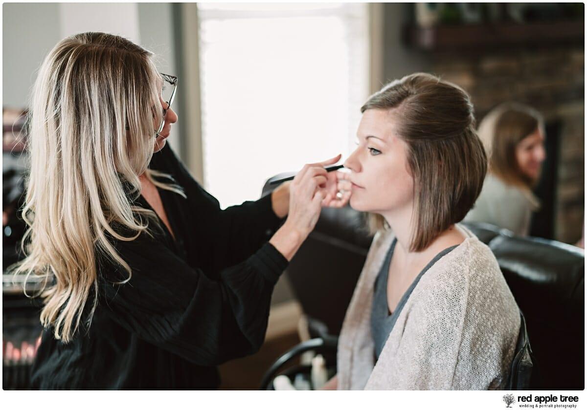 Bride getting wedding makeup